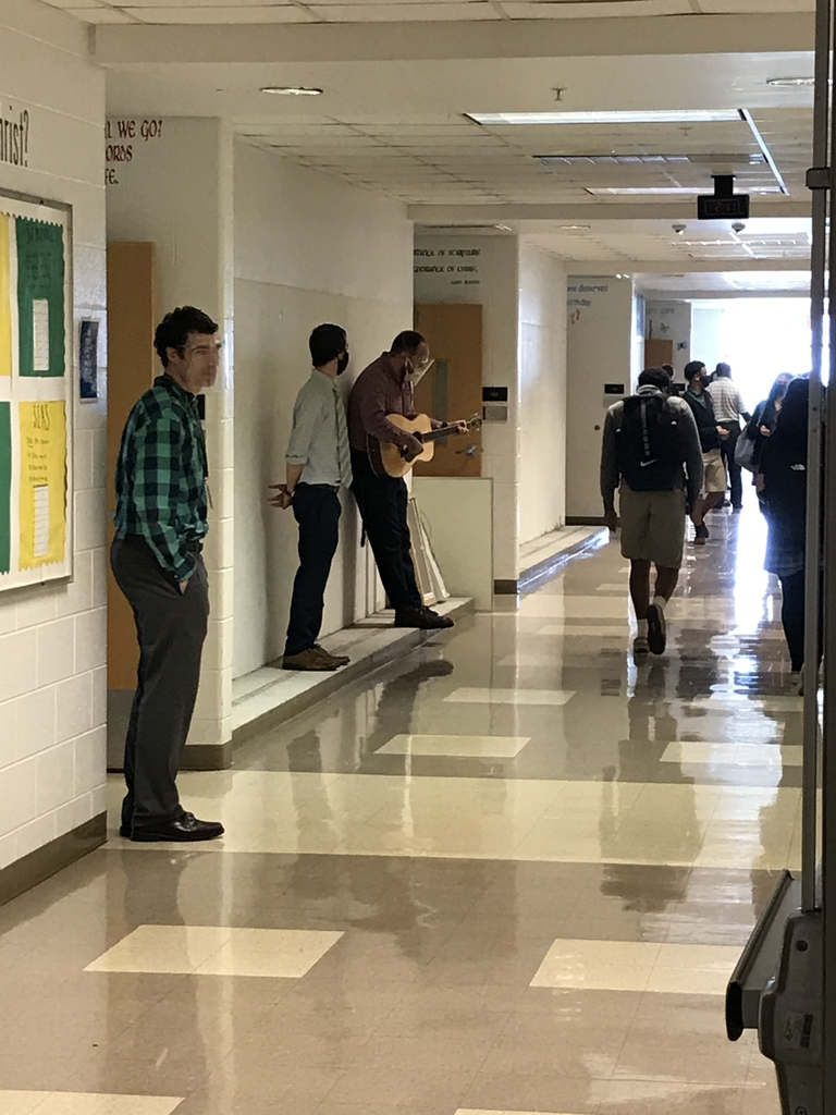 Mr. Mahoney playing guitar in the hall.